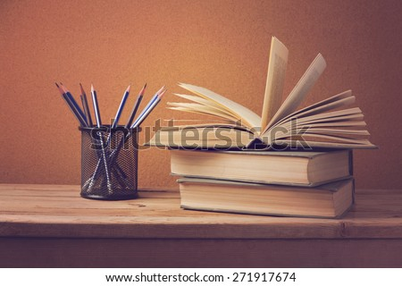 Open book and pencils on wooden deck table