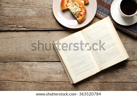 Open book and snack on wooden table background - stock photo