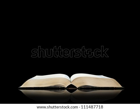 Open book, black background, space for text - stock photo