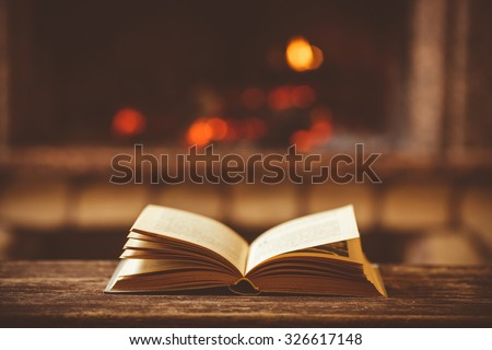 Open book by the Fireplace with Christmas ornaments. Open storybook lying on a wooden bench by the fireside. Cozy relaxed magical atmosphere in a chalet house decorated for Christmas. Holiday concept. - stock photo