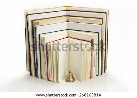 Open book facing one another on a white reflective background, the foreground stands a bell. - stock photo
