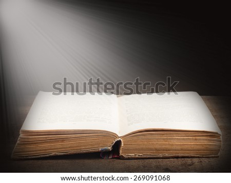 Open book illuminated by bright beam of light on dark abstract background - stock photo
