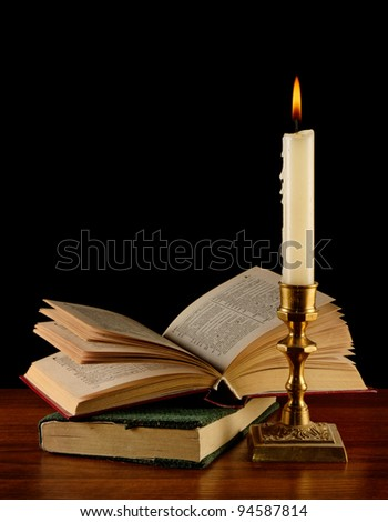 open book illuminated by candle in retro candlestick - stock photo