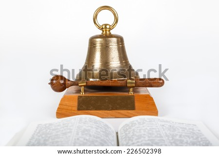 Open book in front and meeting bell behind on the table - stock photo