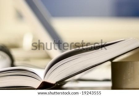 Open book is on office table leaning on a sticking tape