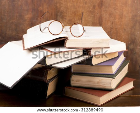 open book, lying on the bookshelf with a glasses - stock photo