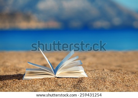 Open book on a beach - stock photo