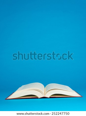 Open book on a blue background with copy space - stock photo