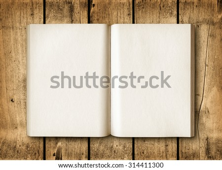 Open book on a brown wood table. Mockup