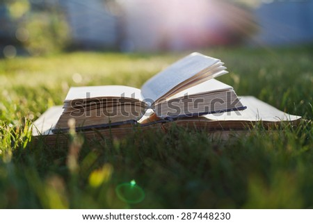 Open book on a green grass against beautiful sunset lights with sun ray, selective focus and shallow dof - stock photo