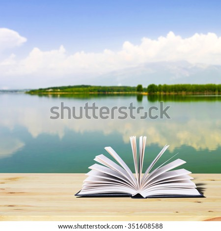 Open book on a rustic wooden table. In the background, the lake, the mountains and the forest - stock photo