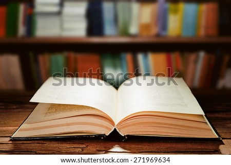 Open book on bookshelves background