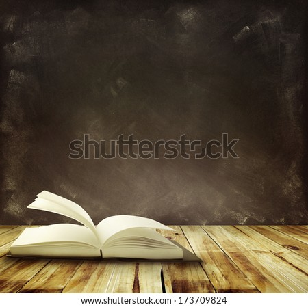 Open book on floor in front of blackboard - stock photo