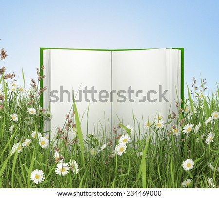 open book on green grass - stock photo