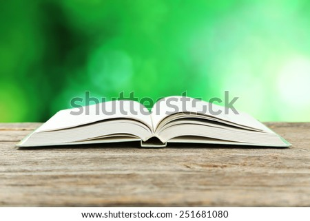 Open book on grey wooden background