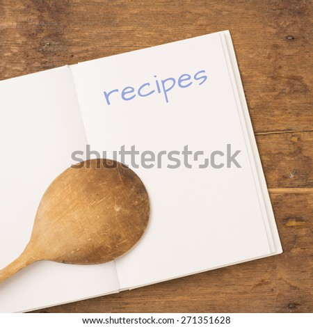 Open book on rustic table with blank white pages with wooden spoon on top.  Empty space for copy or to use as mockup. - stock photo