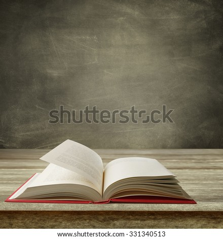 Open book on table in front of blackboard