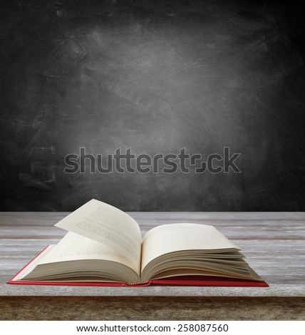 Open book on table in front of blackboard. Copy space