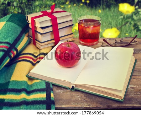 Open book on table in garden. Still life with books and apple - stock photo