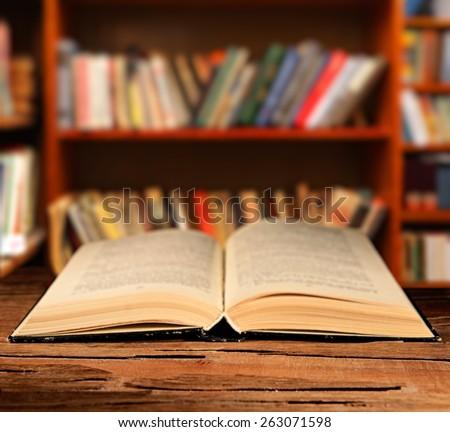 Open book on table on bookshelves background - stock photo