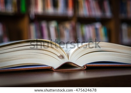 Open book on the table in a library and bookshelf in the background