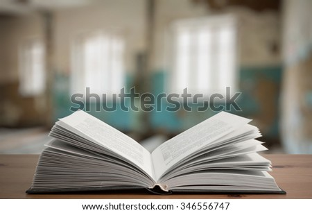 open book on vintage wooden table in old room