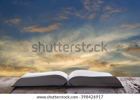 Open book on wood table and sunset as background