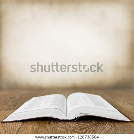 Open book on wood table over grunge background - stock photo