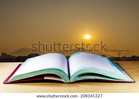 Open book on wood table over Sunrise background