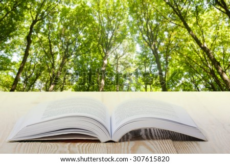 Open book on wooden table on natural blurred background. Back to school. Copy Space