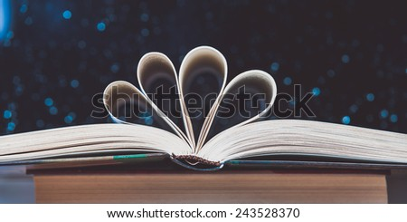 Open book on wooden table with bokeh effect in the backgroun, vingate edition