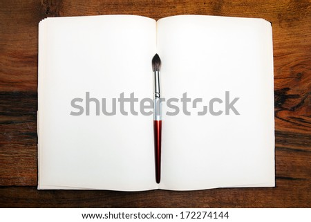 Open book on wooden table with paint brush. - stock photo