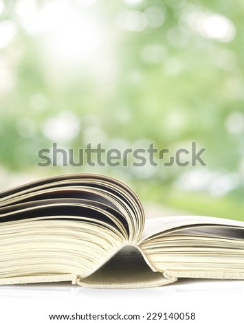 Open book, outdoors, close up,trees blurred in the background - stock photo