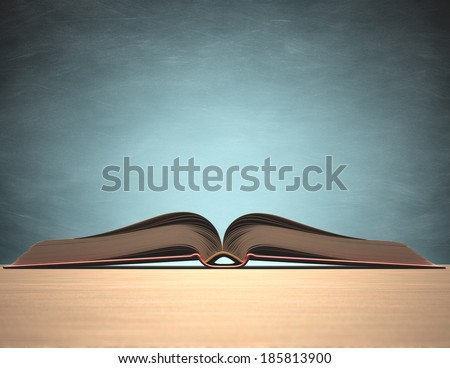 Open book over the table with blackboard on background. Clipping path included. - stock photo
