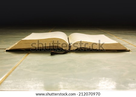 Open book placed on tiled floor.  Virtual opened lighting in the darkness.