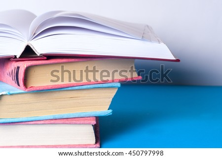 Open book, stack of colorful hardback books on light table. Back to school. Copy space for text. Toned image. - stock photo