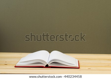 Open book, stack of hardback book on wooden table. Back to school. Copy space. Top view.
