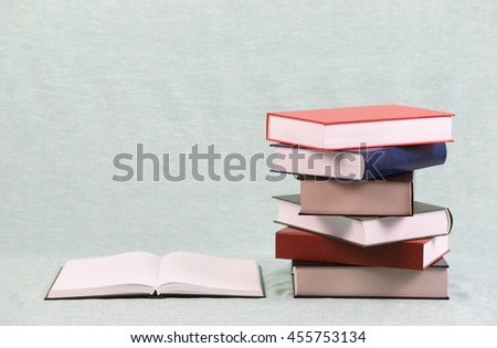 Open book, stack of hardback books on blue table. Back to school. Copy space. - stock photo