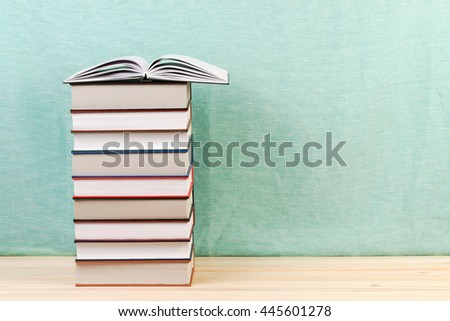 Open book, stack of hardback books on wooden table. Back to school. Copy space. - stock photo