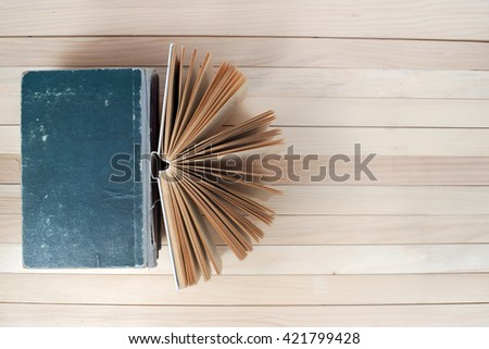 Open book, stack of hardback books on wooden table.  Back to school. Copy space. Top view. - stock photo
