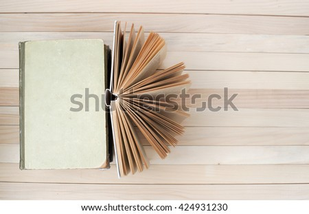 Open book, stack of hardback books on wooden table. Back to school. Copy space. Top view.