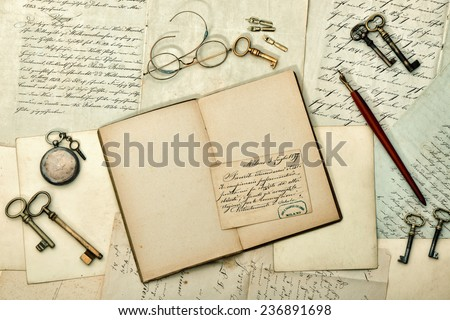 open book, vintage accessories, old letters and postcards. nostalgic aged paper background. retro style toned picture - stock photo
