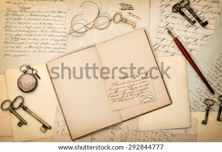 Open book, vintage accessories, old letters and postcards. Nostalgic paper background