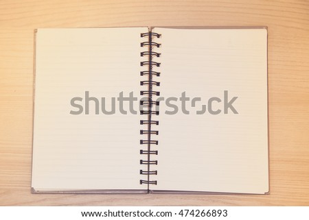 Open book with blank page on wooden table background; single vintage notebook