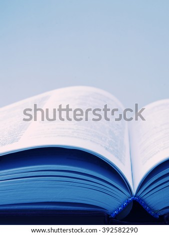 Open book with blurred pages (in blue tones, retro style) with copy space for your text - stock photo