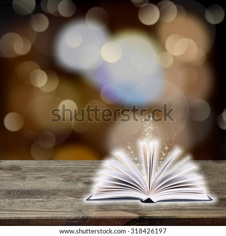 Open book with bokeh light on dark abstract background