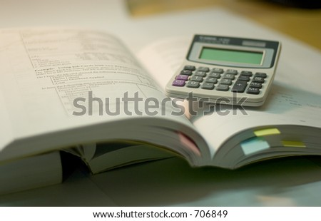 open book with calculator, soft focus - stock photo