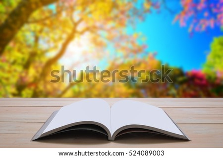 open book with colorful tree background