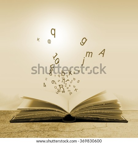 Open book with flying letters. Concept of the importance of reading. Sepia tones. - stock photo