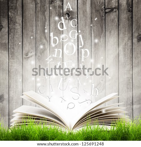 Open book with flying letters in green grass over wooden background. Magic book - stock photo